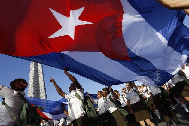 Estudiantes sostienen una bandera de Cuba durante el desfile por el Día Internacional de los Trabajadores, el 1 de mayo, en La Plaza de La Revolución de La Habana. Crédito: Jorge Luis Baños/IPS