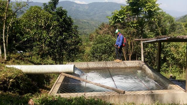 Un hombre muestra el tanque de carga, de 27 metros cúbicos, del sistema hidroeléctrico comunitario de La Taña, uno de los cuatro ya instalados en una montañosa y aislada región poblada mayoritariamente por indígenas, en el noroccidental departamento de Quiché, en Guatemala. Crédito: Edgardo Ayala/IPS
