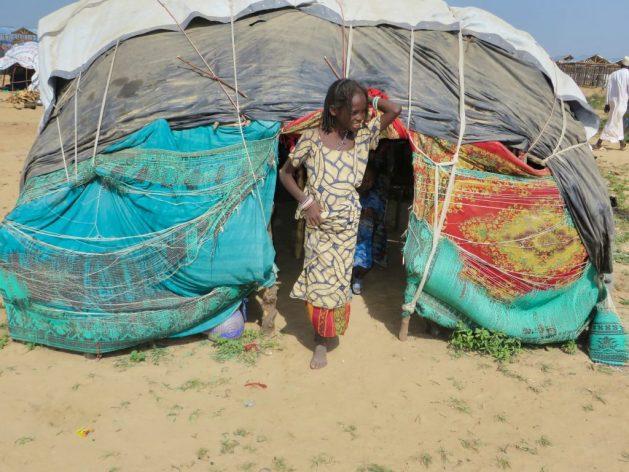 Una niña cuya familia huyó de los combatientes de Boko Haram en la entrada de una tienda de campaña en un campamento para desplazados internos en Maiduguri, la capital del estado de Borno, en el noreste de Nigeria. El extremista grupo islamista ha secuestrado a miles de niñas y las ha convertido en esclavas sexuales y forzado a matrimonios no deseados, entre otros abusos. Crédito: Sam Olukoya/IPS