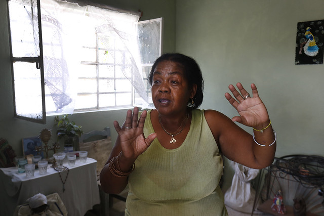 María del Carmen Curbelo, una de las residentes del barrio de La Ciruela, en el municipio de Regla, en La Habana, que sufrió el embate de un gran tornado en enero, cuenta a IPS en la sala de su vivienda recién reconstruida, cómo le impactó ese evento climático que azotó a la capital cubana. Crédito: Jorge Luis Baños/IPS