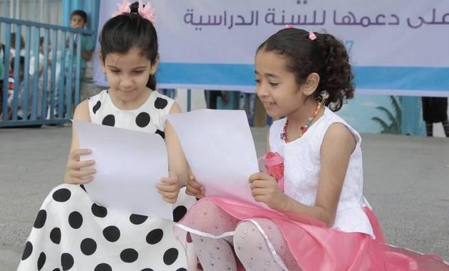 Dos niñas reciben este mes sus certificados escolares, en un centro atendido por la Agencia de las Naciones Unidas para los Refugiados de Palestina. Si no obtiene fondos urgentes, el organismo no podrá iniciar el próximo curso escolar en sus centros en Palestina. Crédito: Mohammed Khalid Adwan/UNRWA