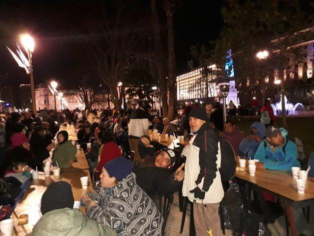 Durante una noche de frío polar en Argentina, personas necesitadas cenan caliente en la Plaza de Mayo, el principal espacio público de Buenos Aires, con la Casa Rosada, sede del gobierno, de telón de fondo. También reciben ropa de abrigo donada. Crédito: Daniel Gutman/IPS
