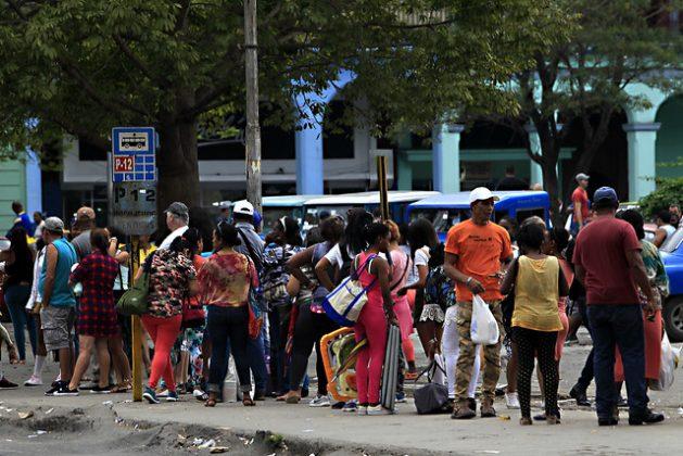Un grupo de personas hace fila en una parada de autobuses del municipio de Centro Habana en la capital de Cuba. El deficitario sistema de transporte público es uno de los problemas que enfrenta la ciudadanía cubana cotidianamente. Crédito: Jorge Luis Baños/IPS