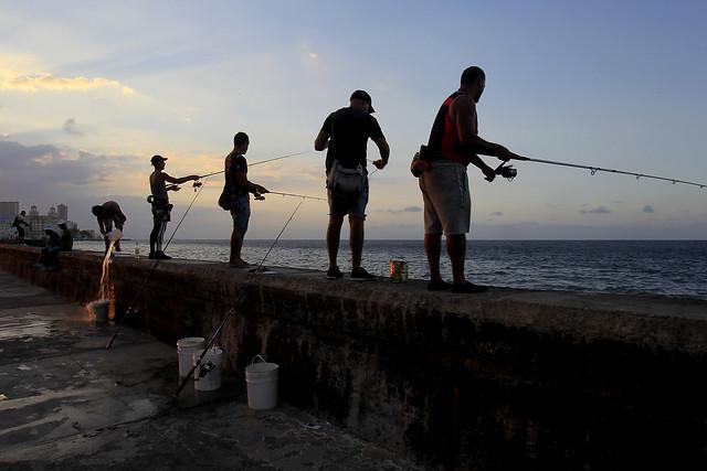 Un grupo de hombres lanza los anzuelos de sus cañas de pesca, desde un muro del malecón de La Habana, en una imagen habitual en la capital cubana. Crédito: Jorge Luis Baños/IPS