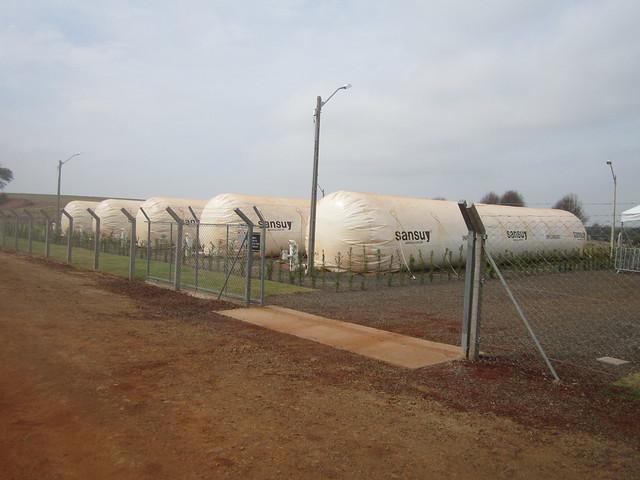 Una hilera de gasómetros, grandes cilindros donde se almacena el biogás que alimentará la Minicentral Termoeléctrica de Entre Rios do Oeste, que genera electricidad con el gas extraído de los detritos de parte de los 155.000 cerdos que se crían en este municipio del estado de Paraná, en el sur de Brasil, en la frontera con Paraguay. Crédito: Mario Osava/IPS