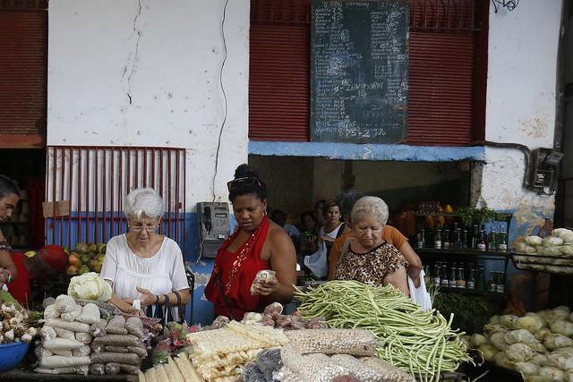 Tres clientas adquieren alimentos en un puesto de un agromercado gestionado por trabajadores por cuenta propia en el barrio del Vedado, en el habanero municipio de Plaza de La Revolución, en Cuba. Crédito: Jorge Luis Baños/IPS