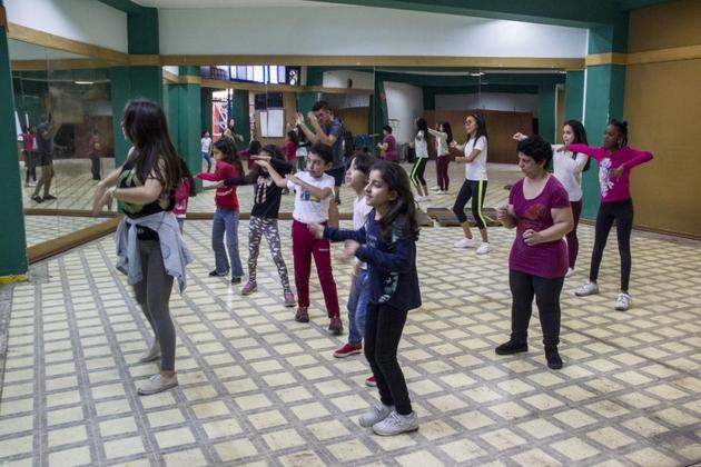 Adrianna, tercera a la derecha, con blusa morada, toma una clase de baile en Ecuador, donde se encuentra entre venezolanos que buscan seguridad. Crédito: Jaime Giménez/Acnur