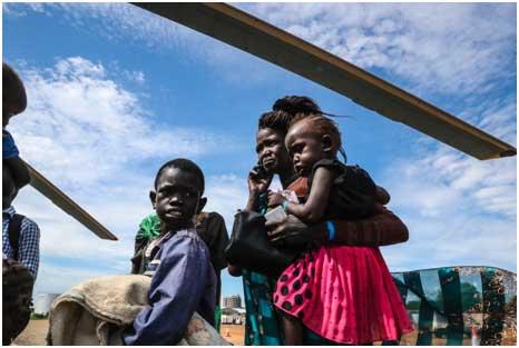 Una madre africana con sus hijos en un campamento de refugiados. Crédito: ONU Mujeres