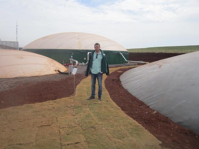 Pedro Kohler, quien lidera la empresa de biodigestores en el oeste del estado brasileño de Paraná, posa entre un biodigestor y depósitos de biogás y biofertilizantes de la central termoeléctrica que instaló en la hacienda de su familia, en el municipio de Cándido Rondon. Innovadoras tecnologías y equipos, aportados por su socia alemana, la empresa Mele, modernizarán el sector de biogás en Brasil. Crédito: Mario Osava/IPS