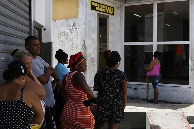 Algunas personas aguardan en las afueras de una oficina de la compañía Western Unión, en el municipio Marianao de La Habana. Esta empresa estadounidense y otras similares canalizan las remesas que los emigrantes cubanos envían a sus familiares. Crédito: Jorge Luis Baños/IPS
