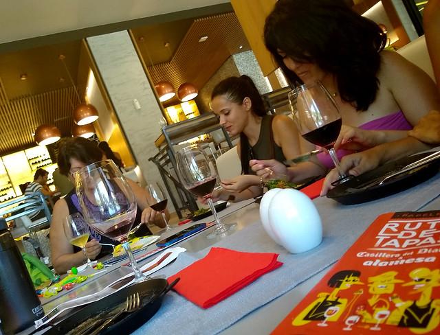 Con el folleto de la Ruta de Tapas Habana al lado, unas clientas degustan los platos que se ofrecen en el hotel Packard, en la capital cubana, dentro de la iniciativa para acercar a la población local a establecimientos dedicados al turismo extranjero. Crédito: Ivet González/IPS