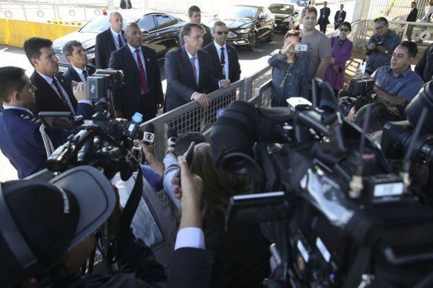 """El presidente brasileño Jair Bolsonaro, durante una de sus informales ruedas de prensa. Esos encuentros, a la entrada del presidencial Palacio del Planalto, se han vuelto casi diarios, a lo que se suma un desayuno semanal con periodistas, pese a las acusaciones del gobernante a la prensa de """"mentirosa"""" o de """"izquierdista"""". En esas ocasiones hace declaraciones de impacto, a veces con ofensas a opositores e incluso miembros del propio gobierno que va a destituir. Crédito: Antonio Cruz/ Agência Brasil"""