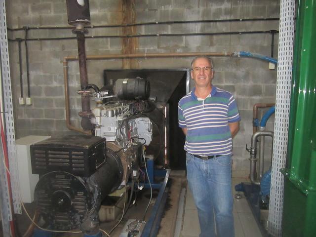 Anélio Thomazzoni junto a uno de los tres generadores eléctricos de su hacienda, en el sur de Brasil. Además de electricidad, el equipo calienta el agua que se bombea por tubos que, introducidos en los biodigestores, elevan la temperatura hasta el nivel adecuado para la fermentación de los excrementos porcinos. Crédito: Mario Osava/IPS