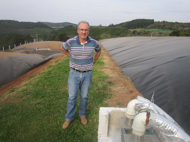 El porcicultor Anélio Thomazzoni entre los tres biodigestores con los que actualmente produce el biogás para la generación de 280.000 kilovatios/hora en su granja, en el pequeño municipio de Vargeão, en el sur de Brasil. Parte del biocombustile se purificará para transformarlo en biometano, mientras se instalan 6.000 metros cuadrados de placas fotovoltaicas para generar 130.000 kilovatios/hora. Crédito: Mario Osava/IPS