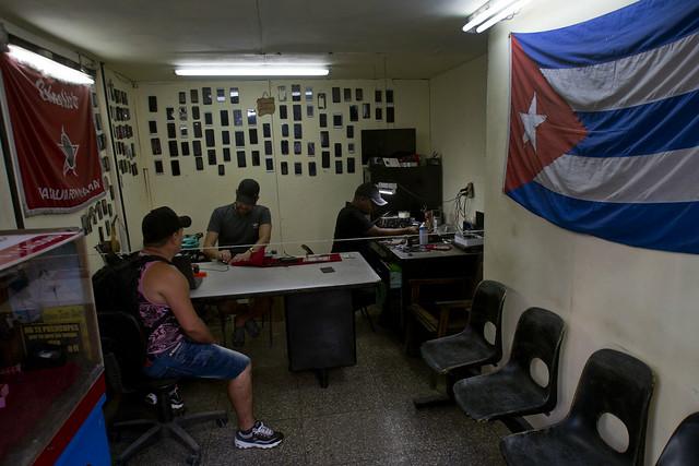 La bandera cubana decora el interior de un establecimiento que presta servicios de reparaciones a equipos electrónicos, en el municipio capitalino de Centro Habana. Los negocios privados como este se incrementa en Cuba, pero su desarrollo afronta ahora la prueba de la agudización de la crisis económica. Crédito: Jorge Luis Baños/IPS