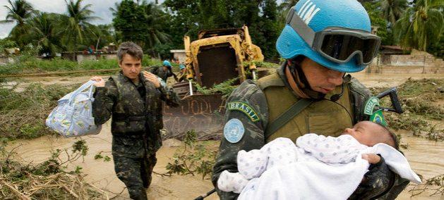 Un miembro brasileño de las fuerzas de mantenimiento de la paz de las Naciones Unidas rescata a un niño después de que partes de la capital de Haití, Puerto Príncipe, se inundaran durante una tormenta tropical en 2007. Crédito: Marco Dormino/ONU
