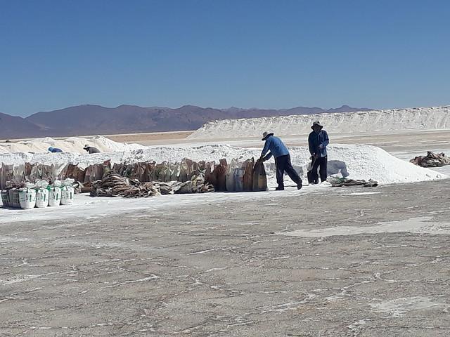 Dos hombres de las comunidades indígenas que viven en los alrededores de Salinas Grandes acopian la sal extraída por los integrantes de la cooperativa local. En Salinas Grandes los asentamientos de su entorno se oponen a que se explote el litio de su subsuelo e impiden que se abra una mina con ese fin. Crédito: Daniel Gutman/IPS