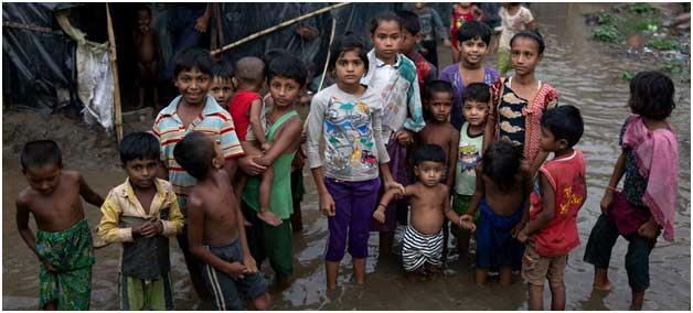 Niños refugiados rohinyá en medio de las aguas que inundan su precario asentamiento en Bangladesh, tras el paso de una tormenta. Crédito: Unicef