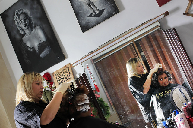 Danilsy Ramírez atiende a una clienta en la peluquería que ha instalado en su vivienda, en el barrio de Boyeros, alejado de la parte más céntrica y turística de La Habana, en Cuba. Crédito: Jorge Luis Baños/IPS
