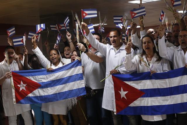 Integrantes de la brigada médica cubana que prestaba servicios de salud en Bolivia entonan las notas del himno nacional de Cuba después de su llegada al aeropuerto internacional José Martí, en La Habana, el 16 de noviembre. Crédito: Jorge Luis Baños/IPS