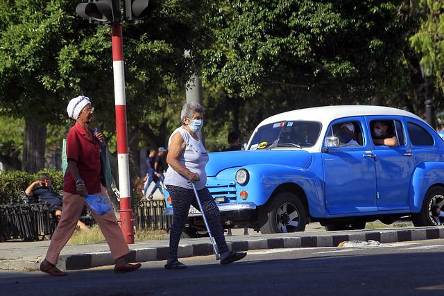 Dos adultas mayores, solo una con mascarilla protectora, cruzan una calle del casco histórico de la capital de Cuba, unas horas antes que las autoridades anunciaran medidas más restrictivas de control y prevención ante el coronavirus. Foto: Jorge Luis Baños/IPS
