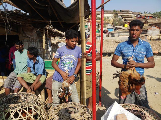 Vendedores de pollo en el mercado del campo de refugiados rohinyás de Kutupalong en Cox's Bazar, antes de que en Bangladesh se decretarse el 26 de marzo la cuarentena nacional para contener al coronavirus. Desde entonces, los rohinyás están confinados en sus precarias viviendas y no pueden salir del campo, mientras las agencias humanitarias temen el impacto si un brote de covid-19 llega a los 34 hacinados asentamientos del campo. Foto: Rafiqul Islam / IPS