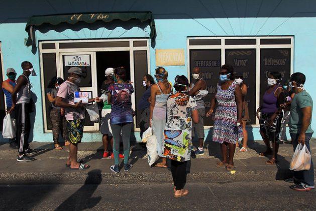 Un grupo de clientes, protegidos con mascarillas y tratando de mantener la distancia entre ellos, aguarda su turno fuera de un establecimiento estatal para la compra de alimentos, en el municipio de Plaza de Revolución, en La Habana, en Cuba. Foto: Jorge Luis Baños/IPS