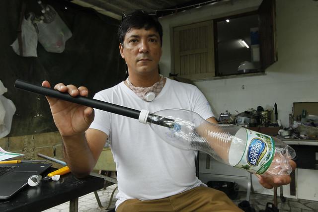 El diseñador Jorge Luis de la Fuente muestra un accesorio construido con botellas de plástico para la elaboración de piezas de plomería, que sirven para hogares y fuentes de uso artístico, en su casa en un barrio periurbano del municipio de El Cotorro, uno de los 15 que conforman la capital de Cuba. Foto: Jorge Luis Baños/IPS
