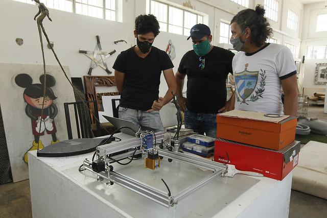 De izquierda a derecha, los creadores Enmanuel y Erick Carmona conversan con el artista plástico Rafael Pérez junto a una máquina que han desarrollado para realizar cortes por plasma a pequeña escala, en su taller en el municipio de Playa, en La Habana. Foto: Jorge Luis Baños/IPS