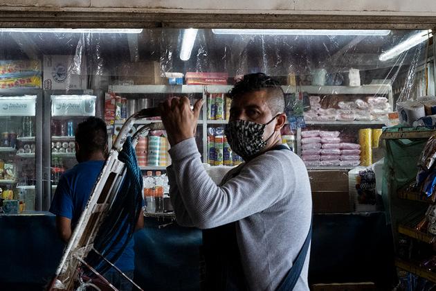 Un acarreador pasa frente a una tienda de comestibles protegida con plástico al final de uno de los pasillos del mercado. Foto: María Ruiz/Pie de Página