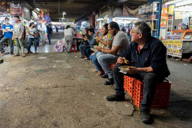 Las taquerías dentro del mercado solo están vendiendo comida para llevar, pero los clientes comen frente a los negocios. Foto: María Ruiz/Pie de Página