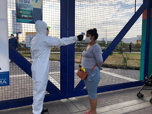 Un operador sanitario chequea la temperatura de una trabajadora antes de entrar a su centro laboral en la capital de Perú. Foto: Municipalidad de Lima