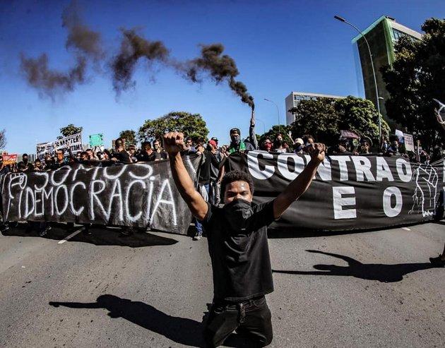 """""""Somos democracia"""", reza una gran pancarta, escogidamente de fondo negro, contra el racismo y el presidente Jair Bolsonaro en Brasilia, también el 7 de junio. Las protestas ciudadanas pueden dar sustento a la inhabilitación del gobernante, que promueven partidos y movimientos sociales, pero aún sin tener el respaldo parlamentario necesario de dos tercios. Foto: Ricardo Stucke/Fotos Públicas"""