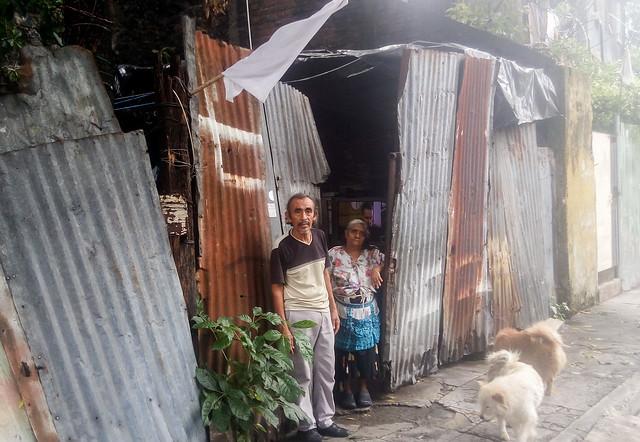 Los vendedores ambulantes René Murgas, de 60 años, y Lucía Cortez, de 73 años, residentes en un precario habitáculo en el sur de San Salvador, se sumaron a las familias que colocaron una bandera blanca fuera de su hogar para indicar su carencia de comida. Y en su caso tuvieron suerte, porque recibieron un paquete de alimentos del gobierno, con espaguetis, aceite, leche en polvo y siete latas de atún. Foto: Edgardo Ayala/IPS