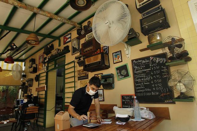 Un empleado toma pedidos para llevar a domicilio, en el interior de la cafetería El Vampirito, administrada por trabajadores privados, en el céntrico barrio de Vedado, en el municipio de Plaza de La Revolución, en La Habana. Los emprendimientos privados han sido impulsados en Cuba por remesas recibidas de familiares en el exterior. Foto: Jorge Luis Baños/IPS