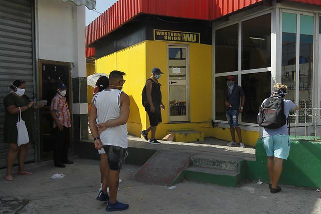 Clientes aguardan su turno en el exterior de una sucursal de la empresa estadounidense de transferencias internacionales Western Union, en Marianao, uno de los municipios de La Habana. Se calcula que a Cuba llegan anualmente en promedio unos 3000 millones de dólares en remesas. Foto: Jorge Luis Baños/IPS