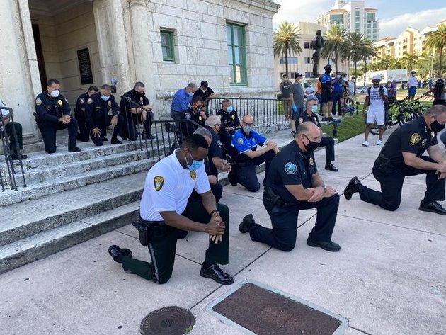 Policías hincados de rodillas en la ciudad de Miami, para rezar y pedir disculpas por la muerte de George Floyd, un gesto en que grupos de agentes han repetido en muchas ciudades de Estados Unidos. Foto: Franklin White/Twitter