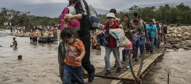 Migrantes venezolanos cruzan en 2019 el río Táchira, en la frontera suroeste de su país, para ingresar a Colombia. Venezuela, Siria, Afganistán, Sudán del Sur y Myanmar son los países con mayor número de sus nacionales desplazados a través de las fronteras en la última década. Foto: Vincent Tremeau/Acnur