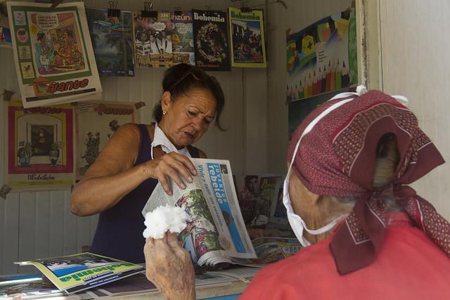 Una empleada vende periódicos a una mujer en un kiosco en el municipio de Playa, en La Habana. Cuba es un país donde los principales medios de comunicación son estatales y no pueden ser privatizados, de acuerdo con la Constitución. Foto: Jorge Luis Baños/IPS