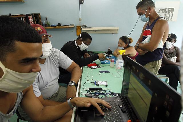 Técnicos en electrónica y reparación de equipos para telefonía móvil y computación ofrecen servicios a clientes en un taller de propiedad privada, en La Habana. Este tipo de negocios ha crecido en los últimos años en Cuba. Foto: Jorge Luis Baños/IPS