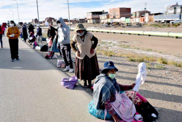 Al borde de la carretera entre Oruro y La Paz, mujeres con sus hijos, buena parte comerciantes informales, se sitúan con banderas blancas a la espera de donaciones de alimentos, tras quedarse abruptamente sin ingresos por la cuarentena, que con diferentes fases, vive Bolivia desde marzo para contener la pandemia de covid-19. Foto: Cortesía de Dehymar Antezana / La Patria