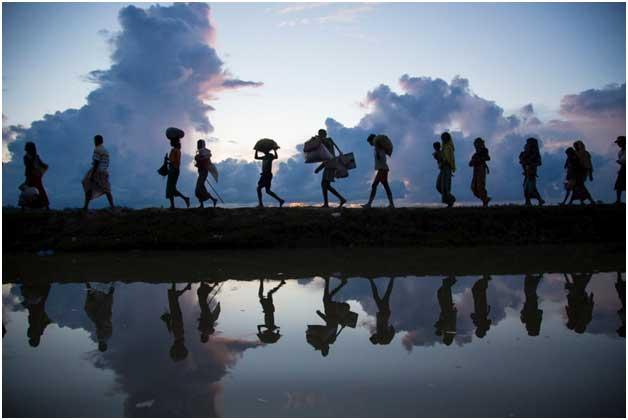 Un grupo de migrantes y refugiados caminan en fila, cargando algunas pertenencias Foto: Acnur