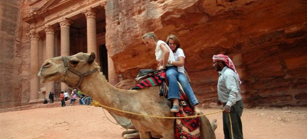 Turistas se disponen a dar un paseo en camello en Petra, en Jordania. La caída en la actividad turística significa un duro golpe para las economías de muchos países,con los del Sur en desarrollo entre los más afectados. Foto: OMT