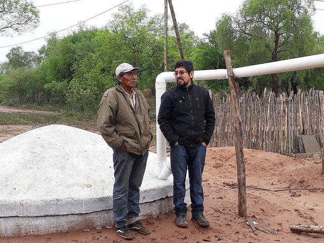 El wichí Mariano Barraza (I) y Enzo Romero, técnico de la organización Fundapaz, junto a la cisterna construida para almacenar agua de lluvia en una comunidad indígena de la provincia de Salta, en la ecorregión del Chaco, en el norte de Argentina, donde hay seis meses anuales de sequía. Foto: Daniel Gutman/IPS