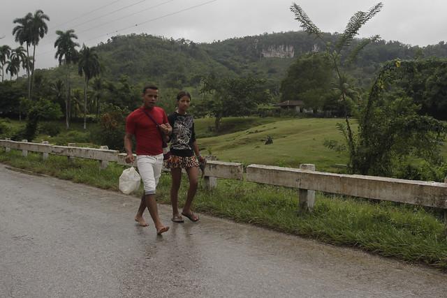 Una pareja joven camina por la carretera que comunica el poblado de Horno de Guisa con la ciudad de Bayamo, en la oriental provincia de Granma, en Cuba. En las áreas rurales prevalecen criterios patriarcales, que otorga a la mujer un rol de su subordinación al hombre en la familia, pese a que la educación y las normas oficiales propugnen la equidad. Foto: Jorge Luis Baños/IPS