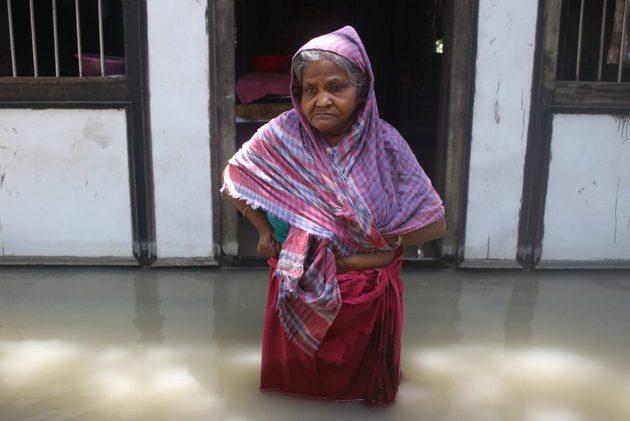 Manju Begum, de 85 años, con el agua hasta las rodillas ante su anegada casa en Medeni Mandal en el distrito de Munshiganj, en el centro de Bangladesh. Ella es una de los casi 5,5 millones de personas damnificadas por las inundaciones en el país y se queja de no haber contado con ninguna ayuda. Foto: Farid Ahmed / IPS