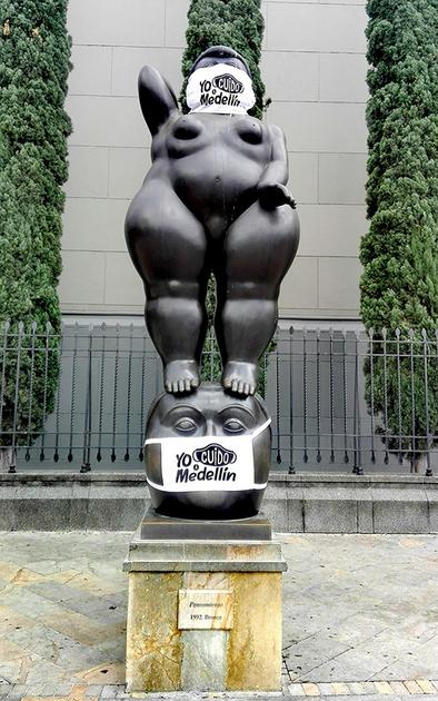 La escultura de una mujer en Medellín, protegida por una mascarilla. Foto: Anderson Ortiz