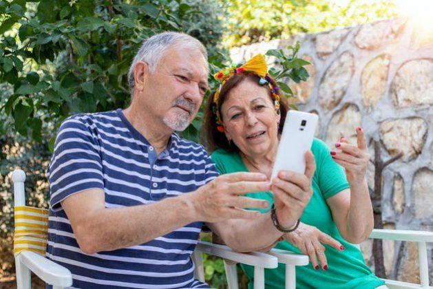 Una pareja de adultos mayores mira la pantalla de un móvil. Foto: Gulcin Ragiboglu/ Shutterstock