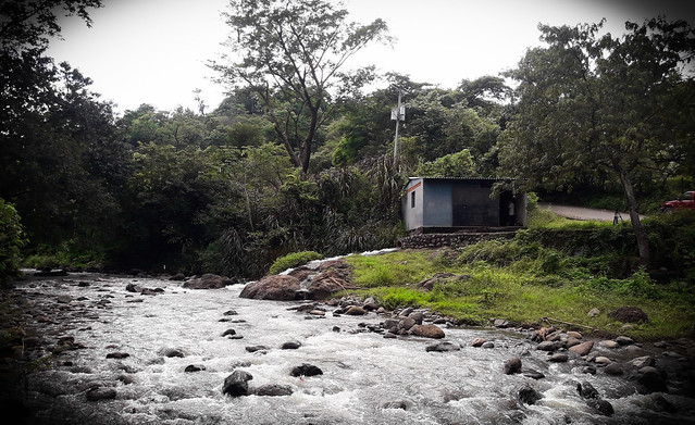 Vista de un segmento del río Carolina, cuyas aguas mueven la turbina que activa el generador que provee de electricidad a los habitantes de los caseríos Potrerillos y Los Lobos, enclavados en las montañas del noreste de El Salvador. Al fondo la casa de máquinas de la minicentral. Foto: Edgardo Ayala /IPS
