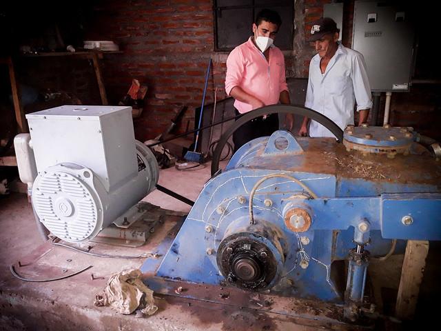 Neftalí Membreño (D), encargado del cuarto de máquinas, revisa el funcionamiento de la turbina y el generador de la minicentral hidroeléctrica del caserío Potrerillos, en el municipio de Carolina, en el departamento de San Miguel, en el este de El Salvador. Esta pequeña comunidad rural, donde viven unas 24 familias, logró en 2006 instalar una pequeña presa para autoabastecerse de electricidad y a bajo costo. Foto: Edgardo Ayala/IPS